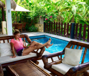 Surf WG Surfcamp Bali a woman is relaxing at the pool in the main villa