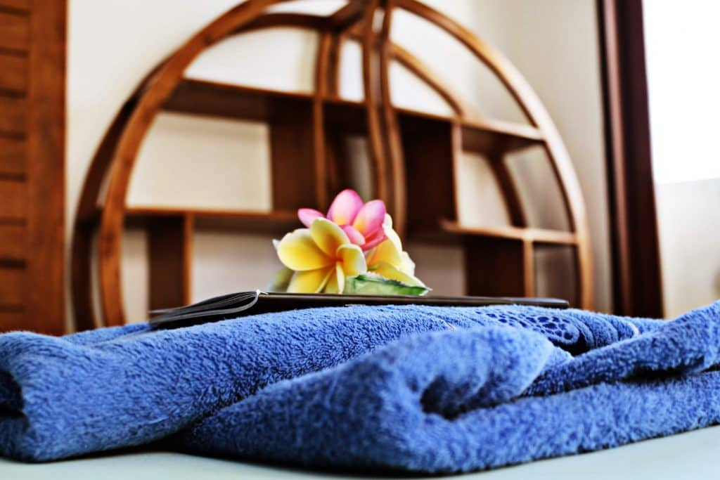 SurfWG towel with yellow and pink flower on top of a bed
