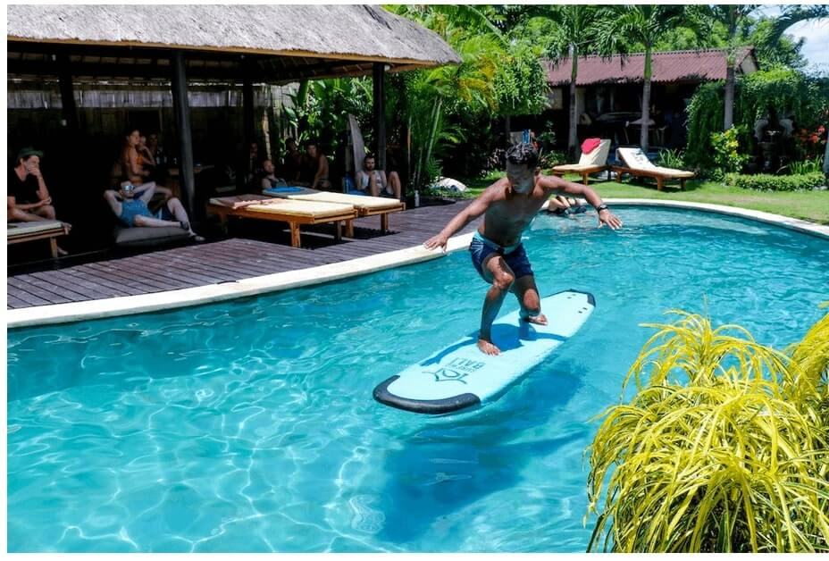 Surf school at surfWG bali surf camp pool training surfguide Eddi2 on surfboard floating in Pool