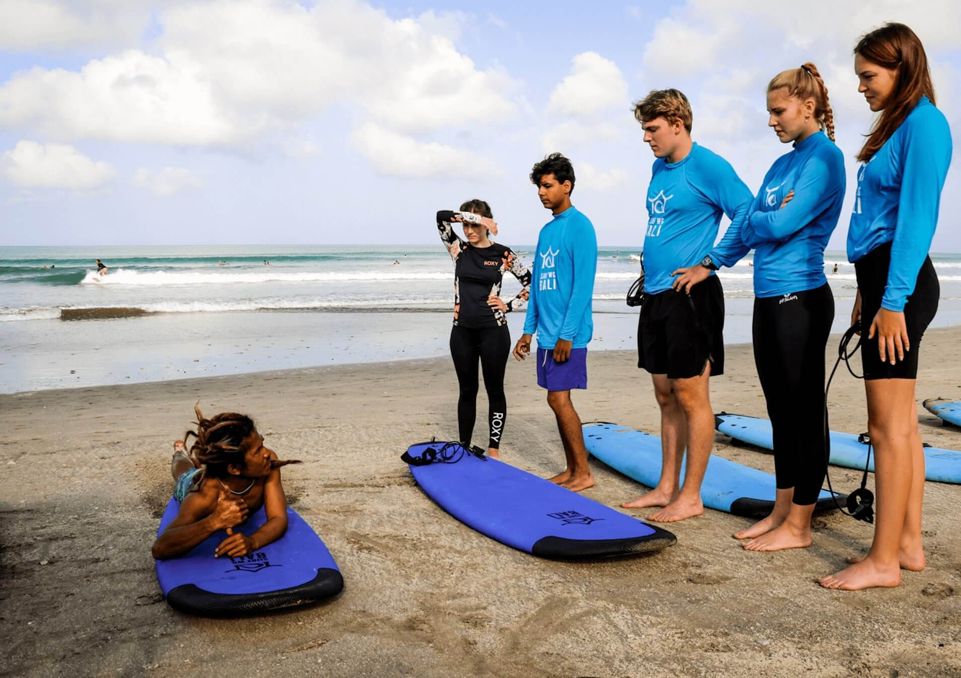 Surf school teacher Bedul at the beach with students in Bali for SurfWG Bali Surf camp